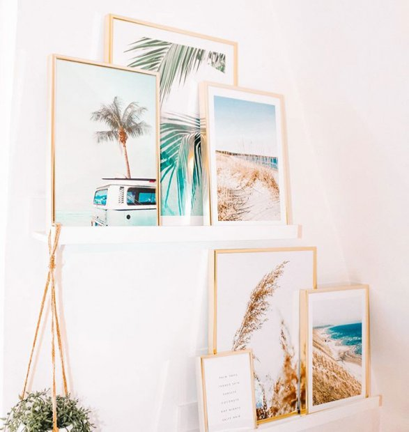 Warm gallery wall with summery posters in oaken frames
